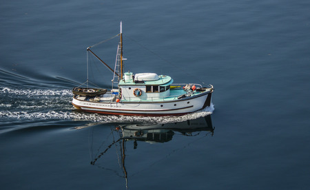 converted: Rustic Converted fishing vessel travelling through ocean Stock Photo