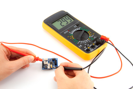 Repair of electronics with digital multimeter in the white background Imagens