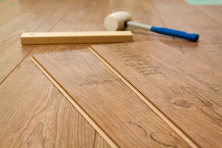 materiales de construccion: Los tablones de suelo laminado y herramientas para instalarlos