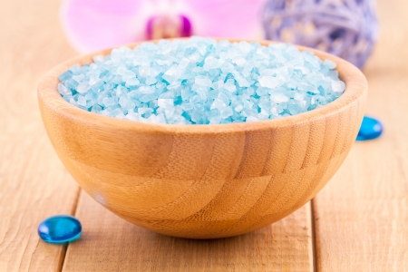 blue Sea salt crystals in a bowl on wood plank photo