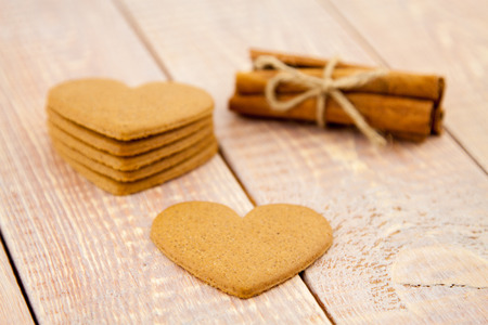 gingerbread heart with cinnamon on wooden planks photo