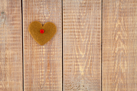 gingerbread heart hanging over wooden background photo