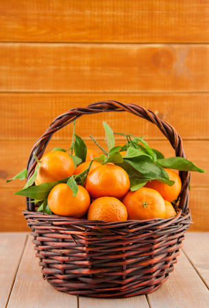 ripe mandarins with leaves in a basket photo