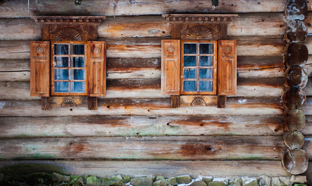 Windows of a wooden snow hut with white landscape reflected photo