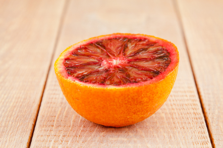 half of ripe red blood orange on the wooden background photo