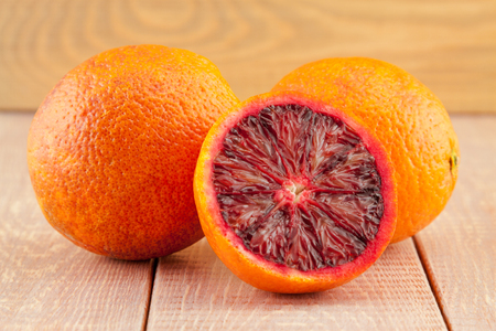 ripe red blood oranges and slices on the wooden background photo