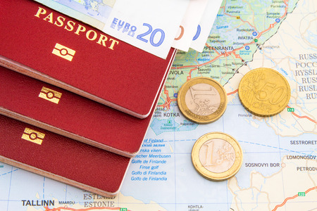 passport on the map with coins and money photo