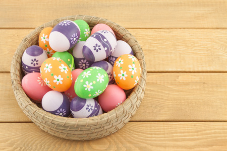 Easter eggs in basket on wooden background photo