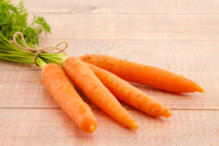 Fresh organic carrots with tops on wooden background photo