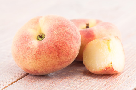 ripe juicy chinese flat peaches on the table photo