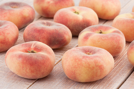 juicy chinese flat peaches on the wood table photo