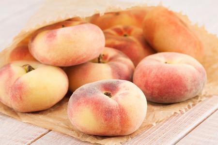 ripe juicy chinese flat peaches or Saturn peaches photo