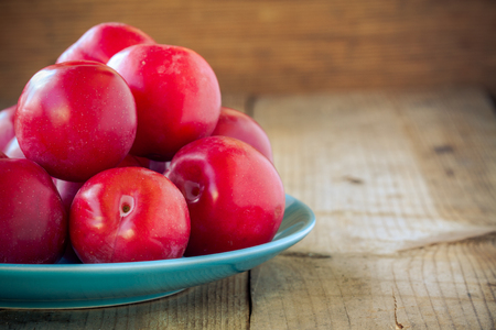 red plums in a blue plate on a wooden background photo