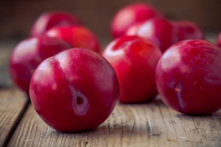 red plums on old rustic wooden background photo
