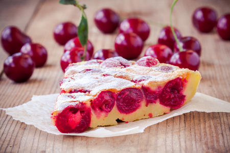 slice of Clafoutis cherry pie on a rustic wooden background photo