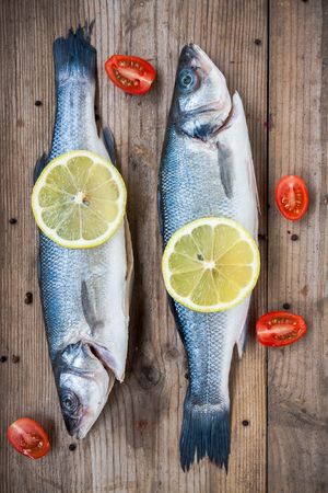 Two raw seabass fish with lemon and cherry tomatoes on a rustic wooden background photo