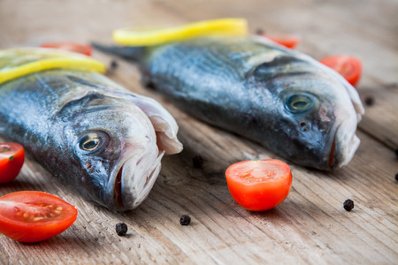 Two raw seabass fish with cherry tomatoes on a rustic wooden background photo