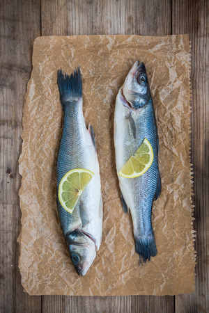Two raw seabass fish with slice of lemon on rustic wooden background photo