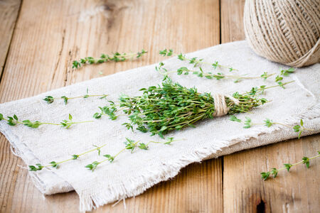 bundle of raw fresh organic thyme on sackcloth photo