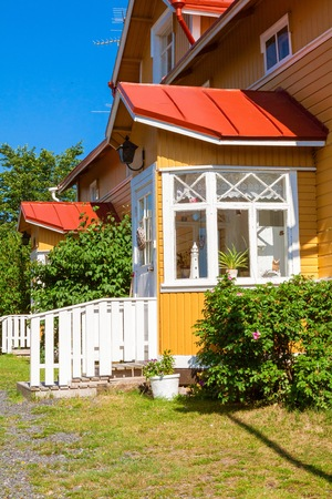Wooden row yellow house with red roof and white windows in Scandinavian style