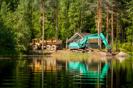 Blue excavator clears the shore of the lake in rural Scandinavia photo