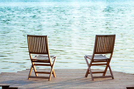 Two adirondack wooden chairs on dock facing a blue lake
