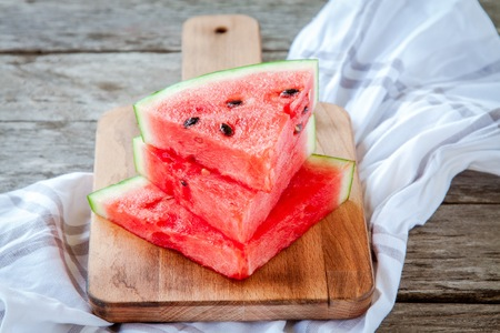 slices of fresh juicy organic watermelon on a wooden background photo