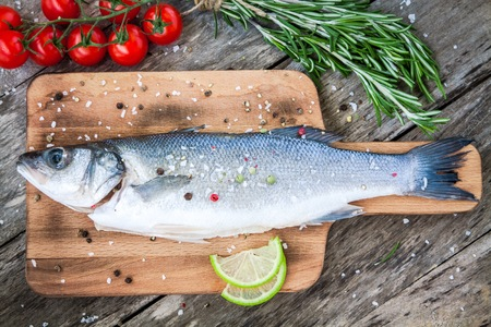 Two raw seabass with lime, cherry tomatoes and rosemary on the wooden background photo