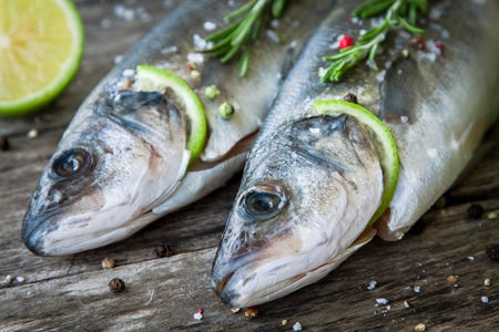 gilthead bream: Two raw seabass with lime and rosemary close up on the wooden background