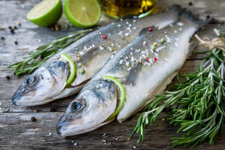 Two raw seabass with lime and rosemary on the wooden background photo