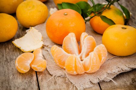 fresh organic mandarins and peeled slices on a rustic wooden background