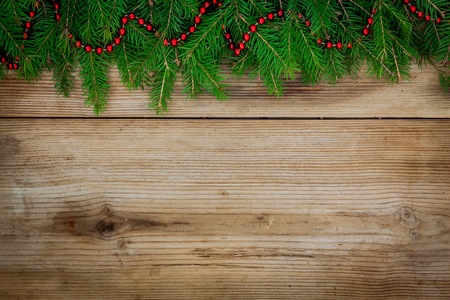 Pine tree border with red garland on old rustic wooden background photo