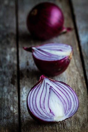 root vegetable: Fresh organic red onions  on a wooden background Stock Photo