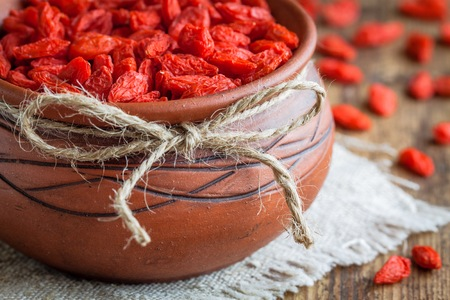 barbarum: goji berries in a clay bowl on a wooden background
