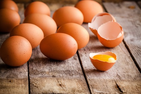 broken egg: Fresh farm eggs on a wooden rustic background