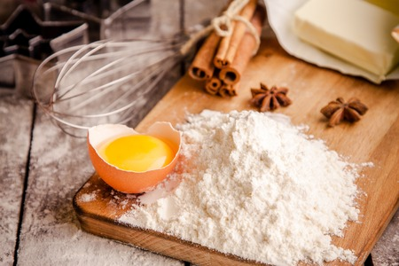 Baking ingredients - flour, eggs, butter and cookie cutters on a table photo