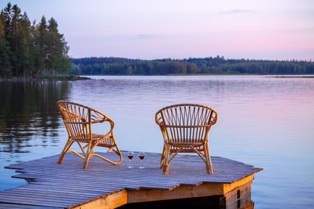 Twee stoelen op dok met glazen wijn Stockfoto