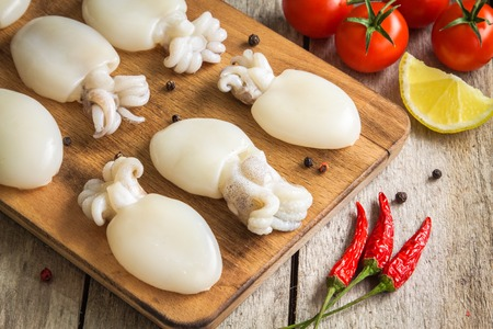 Raw babies cuttlefish  on a cutting board with tomatoes, chili peppers and lemon Stock Photo
