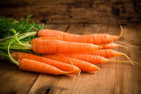 zanahorias: zanahorias frescas mont�n en el fondo de madera r�stica Foto de archivo
