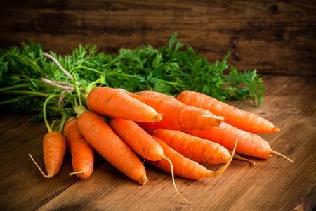 zanahorias: zanahorias frescas montón en el fondo de madera rústica Foto de archivo