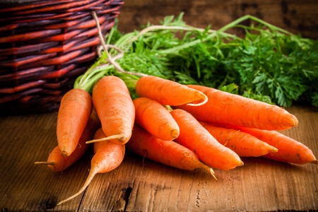 fresh carrots bunch on rustic wooden background photo