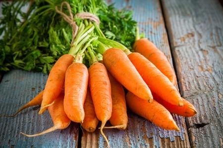 Bündel frische Karotten auf rustikalem Holzuntergrund Standard-Bild - 36483314
