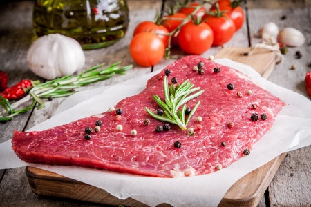 raw meat steak on a cutting board with rosemary and pepper on rustic background photo