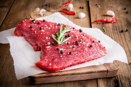raw meat steak on a cutting board with rosemary and pepper on rustic background