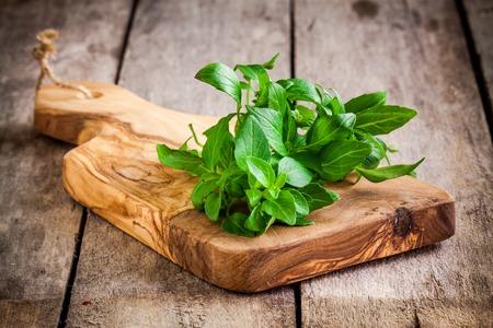 mortero: manojo de albahaca fresca orgánica en la tabla de cortar de oliva en el fondo de madera rústica