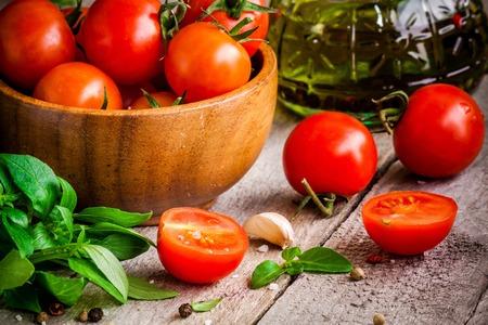 ajo: tomates cherry, albahaca fresca org�nica, ajo, aceite de oliva en el fondo de madera r�stica