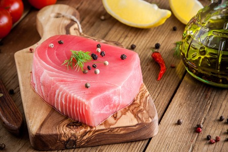 Raw tuna fillet with dill, lemon and peppers in olive cutting board Zdjęcie Seryjne