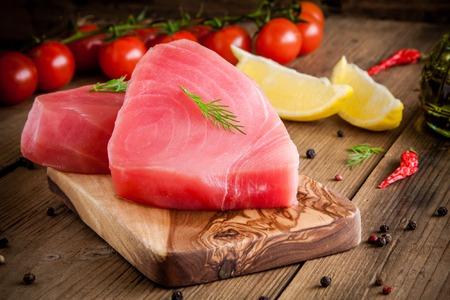 Rauwe tonijn filet met dille, citroen en cherry tomaten in olijfolie snijplank