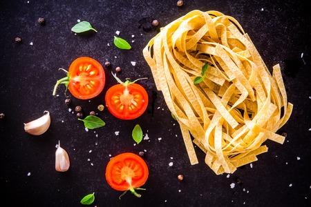 新鮮な有機トマトとバジルと暗い背景にニンニクのフェットチーネ