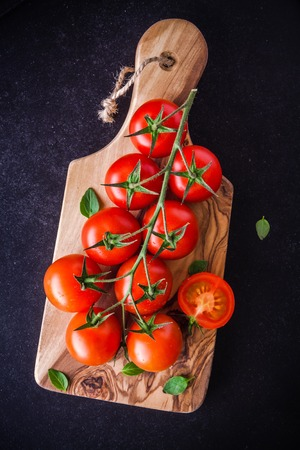 a bunch of fresh organic cherry tomatoes in olive cutting board on a dark background photo